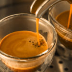 mainstream of strong espresso coffee from a espresso machine to translucent glass cups
