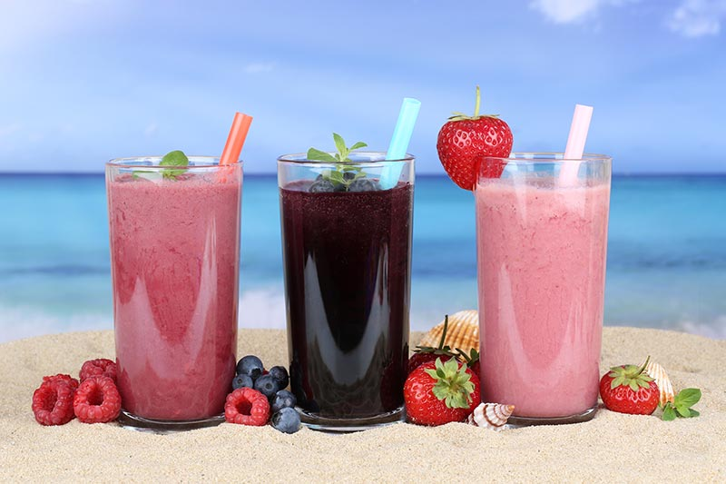 strawberry and blackberry fruit smoothies on the beach